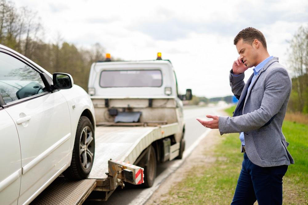 kierowca rozmawia przez telefon przy uszkodzonym aucie