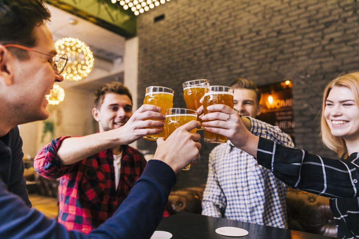 klienci pubu z piwami w dłoniach
