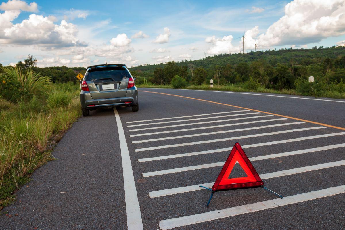 auto stoi na poboczu a przed nim trójkąt ostrzegawczy